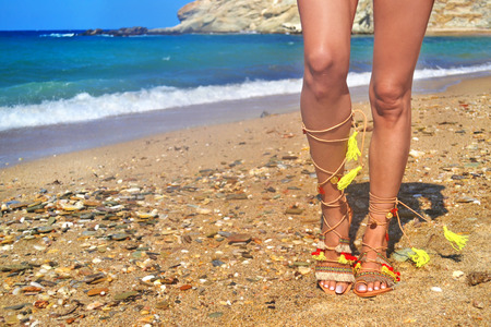 model advertises bohemian greek sandals at the beach - summer shoes advertisement Stock Photo