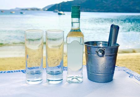 Ouzo grec dans une taverne en face de la mer Banque d'images - 64842588