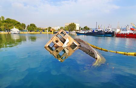 sunken: sunken boat reflected on water at Eleusis Greece