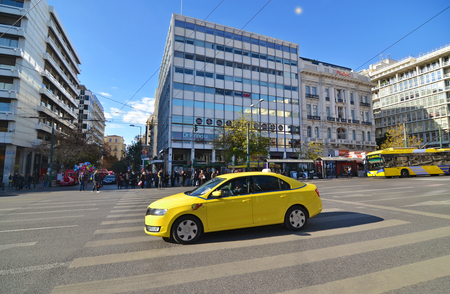 SYNTAGMA ATHENS GREECE, DECEMBER 18 2016: yellow taxi and people waiting to cross the road at Syntagma Athens Greece. Editorial use. Editorial