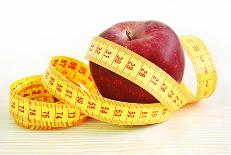 red apple with tape measure - weight loss - diet concept