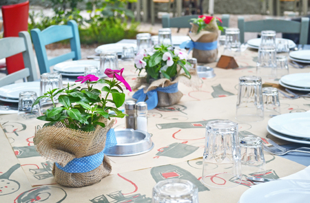 greek pot: table decorated with blooming flower pots at a greek restaurant