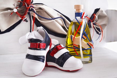 greek Orthodox christening objects - baby shoes and the baptism oil Stock Photo