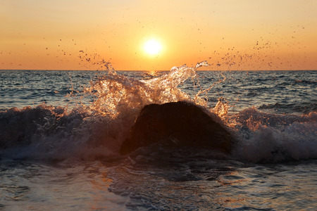 ionio: beach waves hitting the rocks with sunset background at Erimitis beach Paxos island Greece