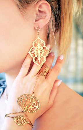 woman wearing expensive gold jewelry - golden bracelet ring and earings Stock Photo
