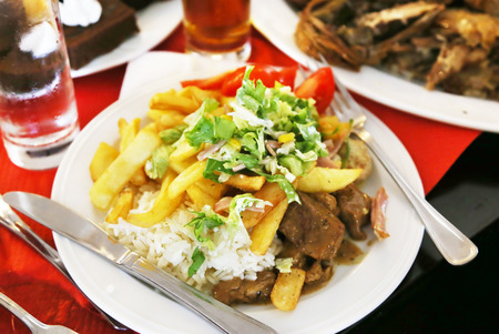 plate with food at a greek restaurant - steak meat with fried potatoes and fresh vegetables