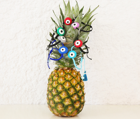 evil eye bracelets advertisement on pineapple - exotic fruit with greek jewelry