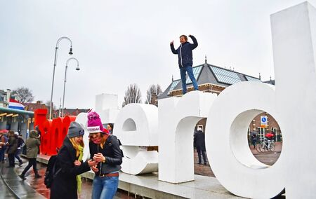 AMSTERDAM HOLLAND, MARCH 29 2015: tourists posing in front of the I Amsterdam slogan Holland. Editorial use. Editorial