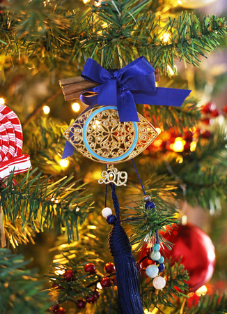 decorative 2019 Christmas lucky charm with cinnamon and blue ribbons on the Christmas tree 写真素材
