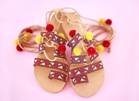 bohemian leather sandals with red tassel and pom pom - gladiator sandals - pink background