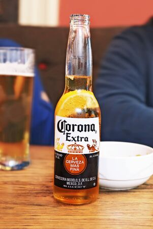 ATHENS GREECE, JUNE 14 2019: Corona beer on a wooden table at a greek night bar. Editorial use.