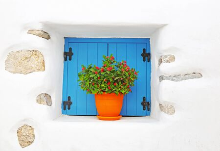 traditional white house with turquoise window and blooming flowers at Koufonisia Greece