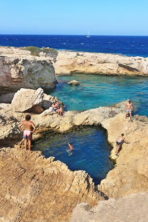 ANO KOUFONISI GREECE, AUGUST 27 2019: people swimming in the natural pool of the sea between the rocks at Ano Koufonisi island Greece. Editorial use.