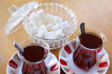 traditional turkish tea with sugar cubes on wooden table