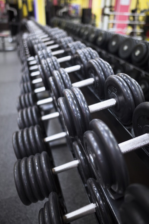 heavy weight: row of dumbbells on a rack in gym Stock Photo