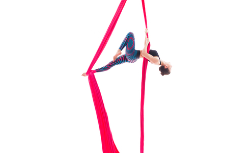 Woman hanging in aerial silks, isolated on white