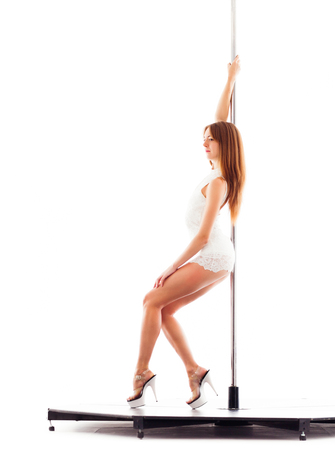 Woman doing striptease pole dance, isolated on white