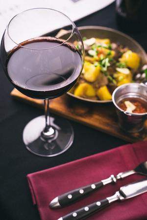 glass of red wine in front of freshly cooked meat Stock Photo