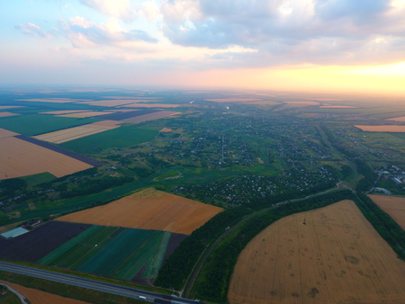 Aerial view of beautiful village, houses, roads. Sky, clouds, sunset. Standard-Bild
