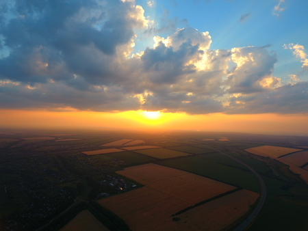 Aerial view of beautiful village, houses, roads. Sky, clouds, sunset. Фото со стока
