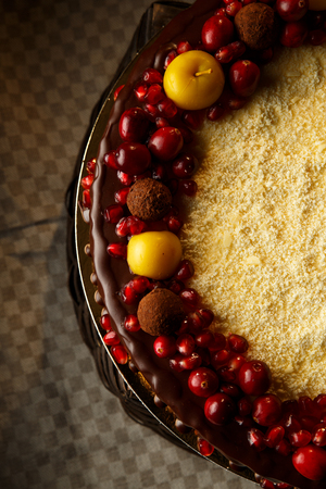 Triple chocolate cake decorated with pomegranate, cranberries and small apples.