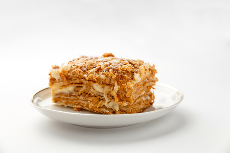 French Napoleon Cake of puff pastry with sour cream on a white plate close-up. Nutritious dessert. Selected Focus Stock Photo