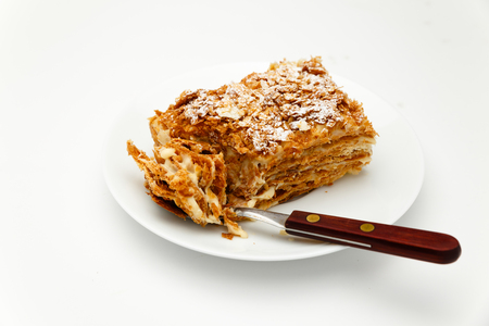 French Napoleon Cake of puff pastry with sour cream on a white plate close-up. Nutritious dessert. Selected Focus. Stock Photo