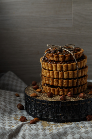 Tower of the delicious cakes with nuts on plate.