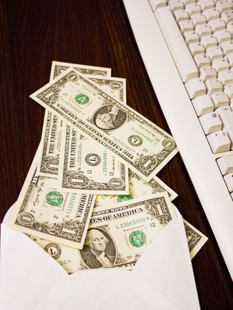 money in envelope next to computer keyboard