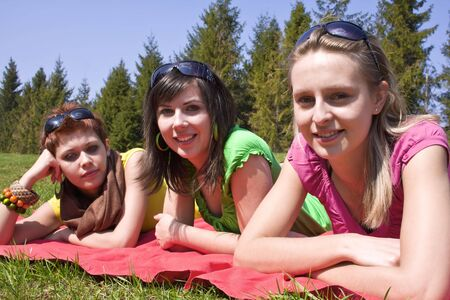 three lovely girls relaxing on meadow 3 photo
