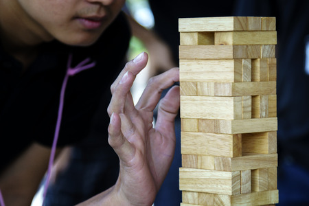 man concentrate during team activity game of wooden jigsaw Zdjęcie Seryjne
