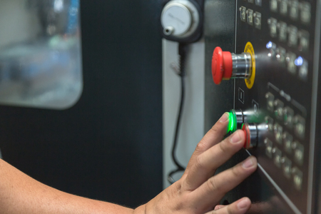 worker press start buttom on panel control of CNC machine