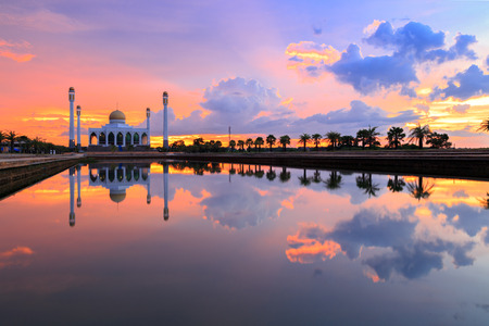 reflection of mosque and sunset sky on water