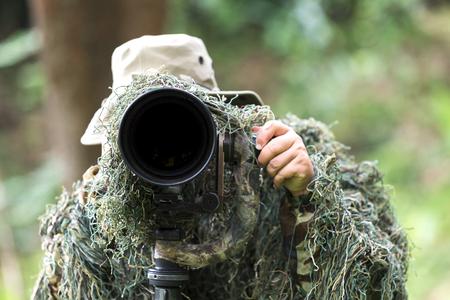 Ornithologist use telephoto len taking photo of bird