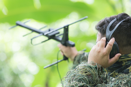 Ornithologist use earphone to check signal to find bird position