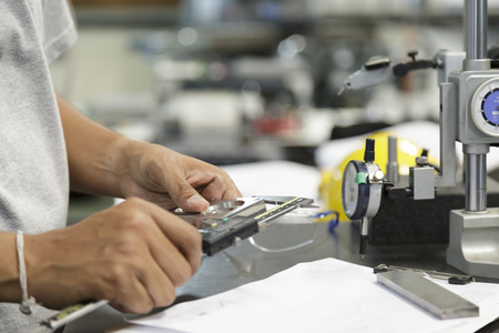 worker use vernier measure precision of machine part