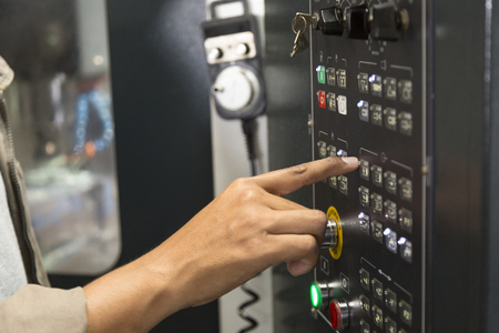 Man press control knob in control panel of CNC machine