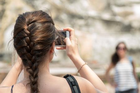 lady taking photo of her friend by mobile phone Zdjęcie Seryjne