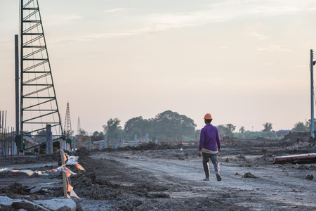 Labor in construction site walking to work during sunset background