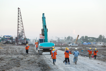 Group of labor and heavy excavator going to work in construction site Zdjęcie Seryjne