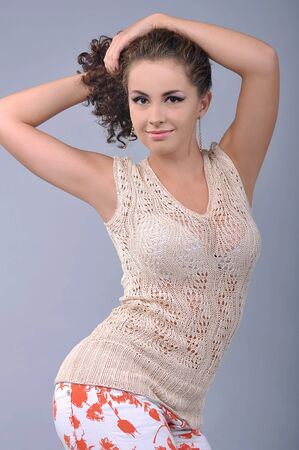 underarms: curly-haired girl posing in a knitted sweater, studio Stock Photo