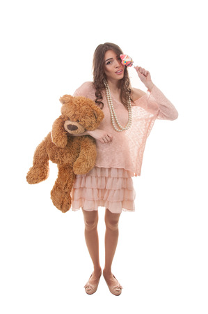 Portrait of cute girl with candy and bear toy
