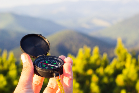 Hand holding compass on summer mountains background