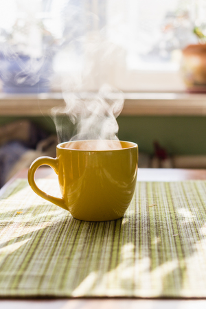 Steam of morning tea above yellow cup on table