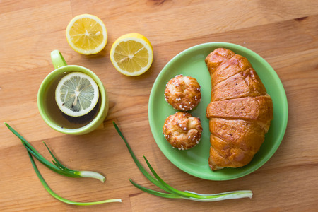 Tea with lemon and croissant for fresh spring breakfast on wooden table Stock Photo