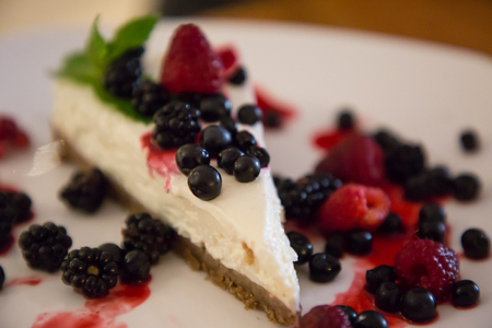 Berry cheesecake with berries on a plate in a caffe