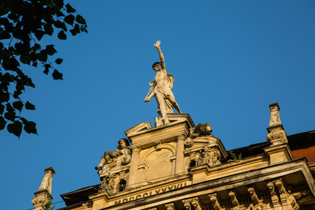 Statue of Mercury - a major Roman god standing on a building facade in city Lviv, Ukraine