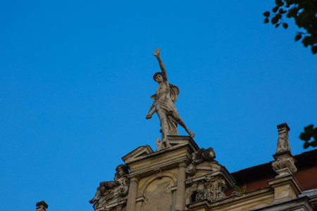 Statue of Mercury - a major Roman god standing on a building facade in city Lviv, Ukraine