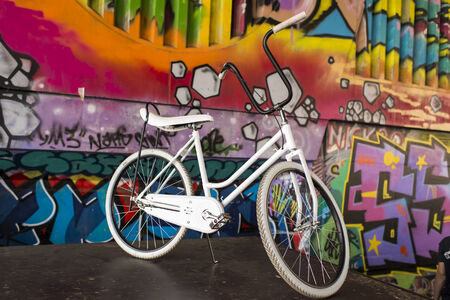 old school bike: White vintage bicycle with graffiti background