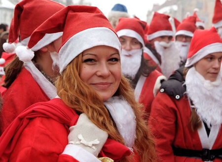 Uzhgorod,Ukraine-December 17, 2010: Smiling girl dressed as a Santa Claust in the front of group of other peaple dressed the same during Santa Claus parade December 17,2010 in Uzhgorod. Ukraine